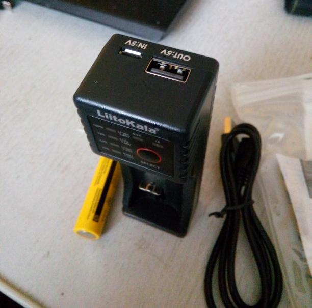 Зарядка Liitokala Lii-100 лежит на белой поверхности рядом со шнуром питания и инструкцией подключения