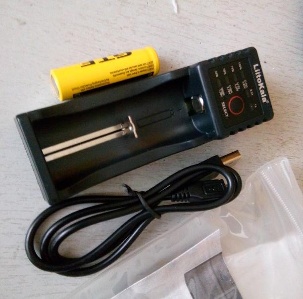 Зарядное устройство Liitokala Lii-100 рядом с прозрачной упаковкой и со шнуром питания. Видно светодиоды.